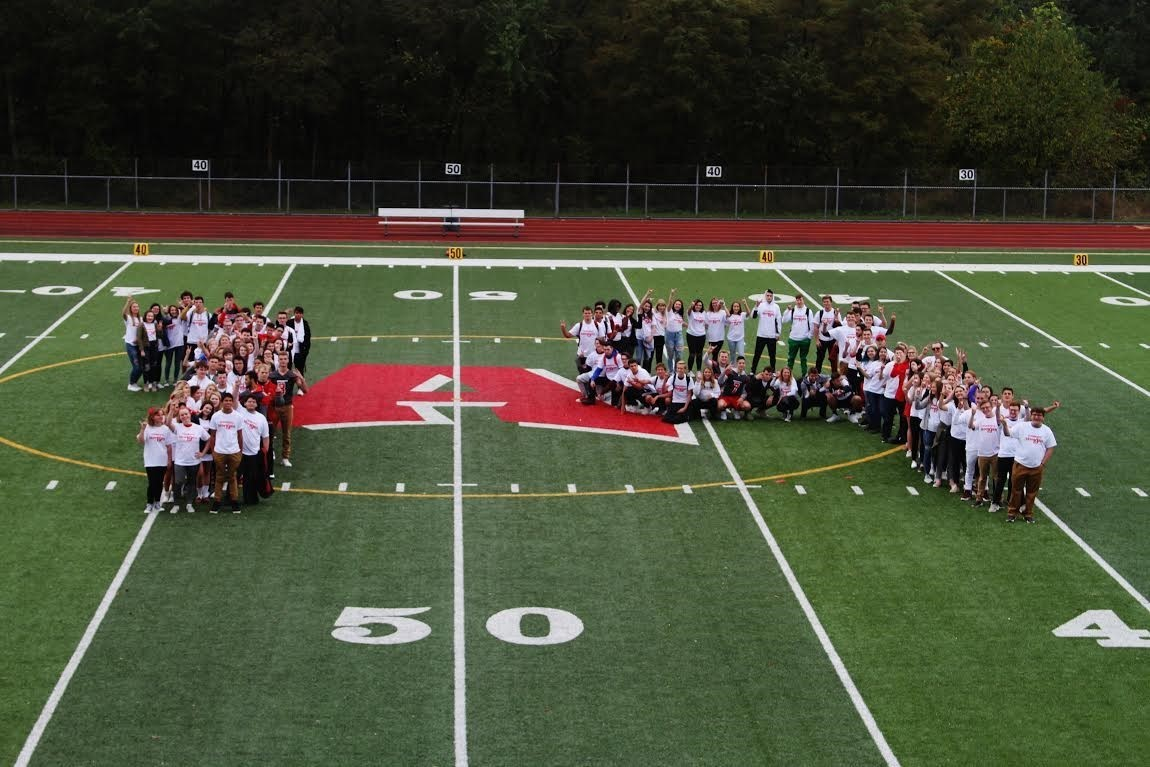 This picture is the entire Class of 2019 (126 students) standing in the middle of the Football Field in the shape of a 19.  The picture is taken from above, in the press box.