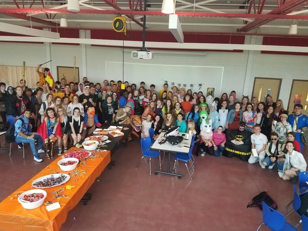 This photo is a group picture of 120 senior students in the Large Group Instruction Room after their Halloween Parade.  Students are grouped together and in costume smiling and enjoying the event!