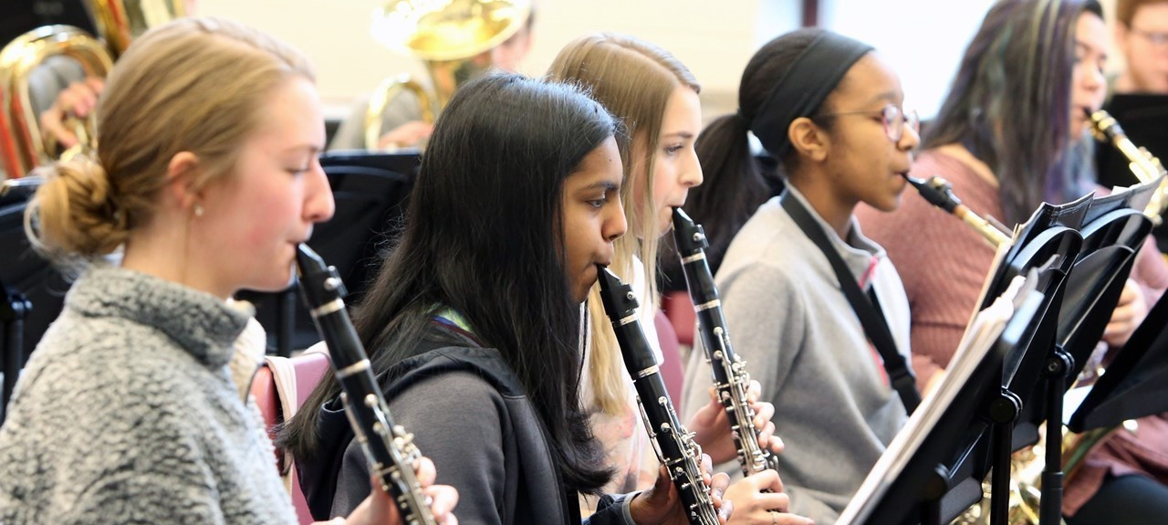 This photo shows 5 female band members playing their instruments - 3 clarinets and 2 saxophones. Close picture showing profile of girls playing.