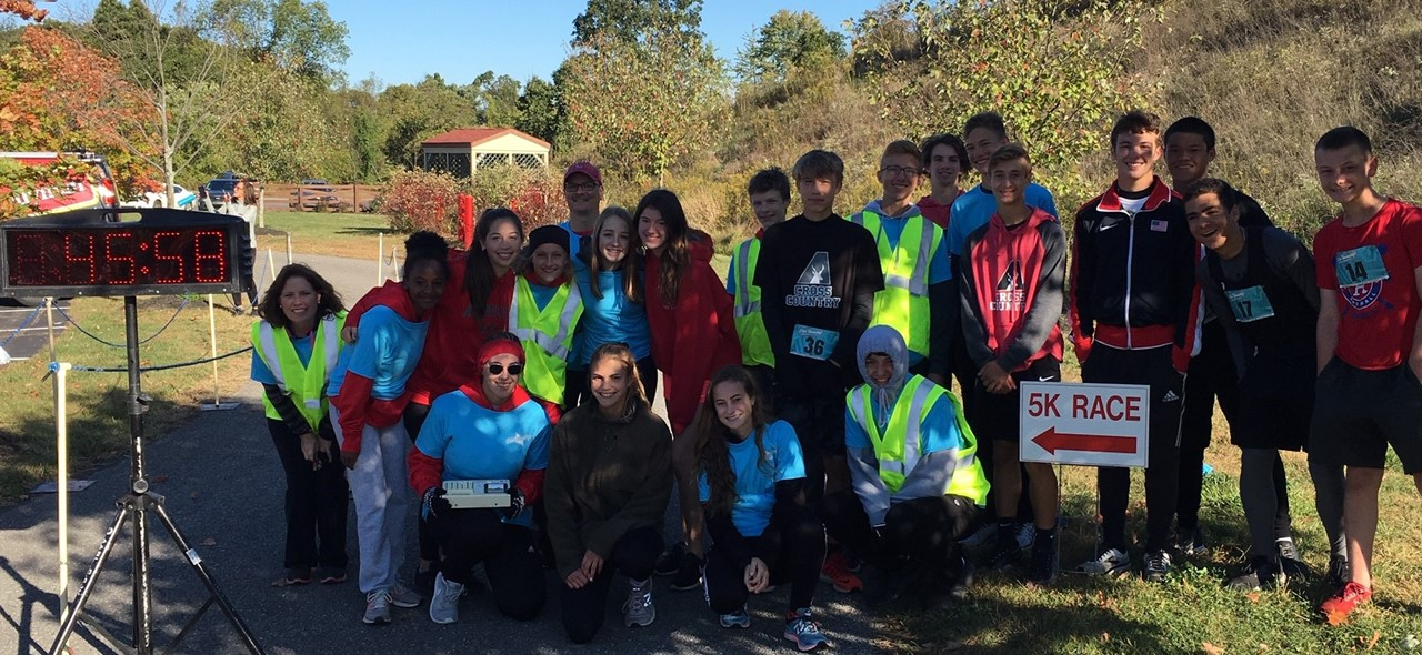 Photo of members of the Avonworth High School Cross Country team as they volunteered their time at the Ohio Twp 5K. Students are posing as a group next to the race clock and finish/start line.