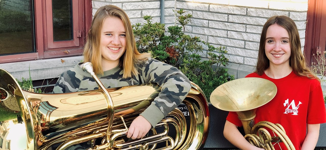 Photo of two avonworth musicians, Jessica and Lea, holding their instruments sitting on a bench outside the sch=ool