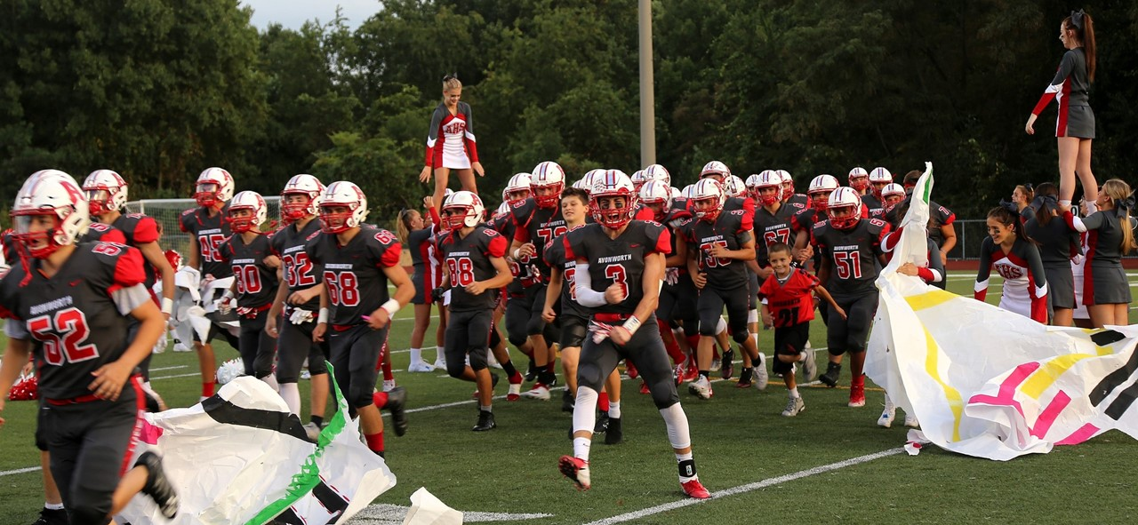 Photo of the Avonworth Football Team breaking through the paper banner as they enter the field at a home football game.  Cheerleaders are also in the background and sides of the team cheering them on.