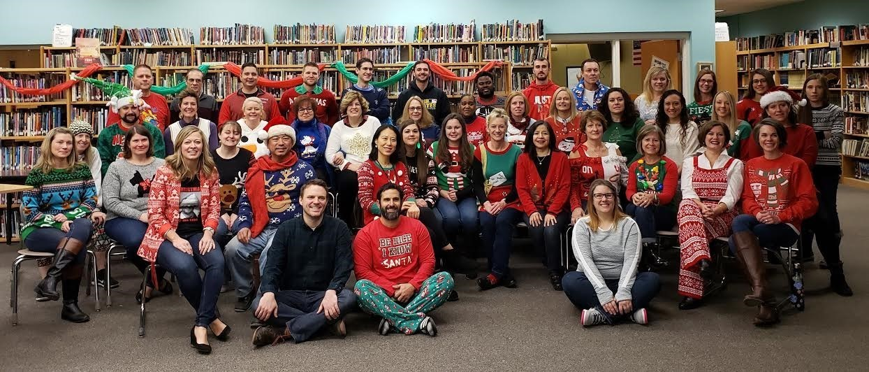 Avonworth HS Faculty and Staff - approximately 50 teachers in Christmas holiday sweaters grouped together smiling in the Library