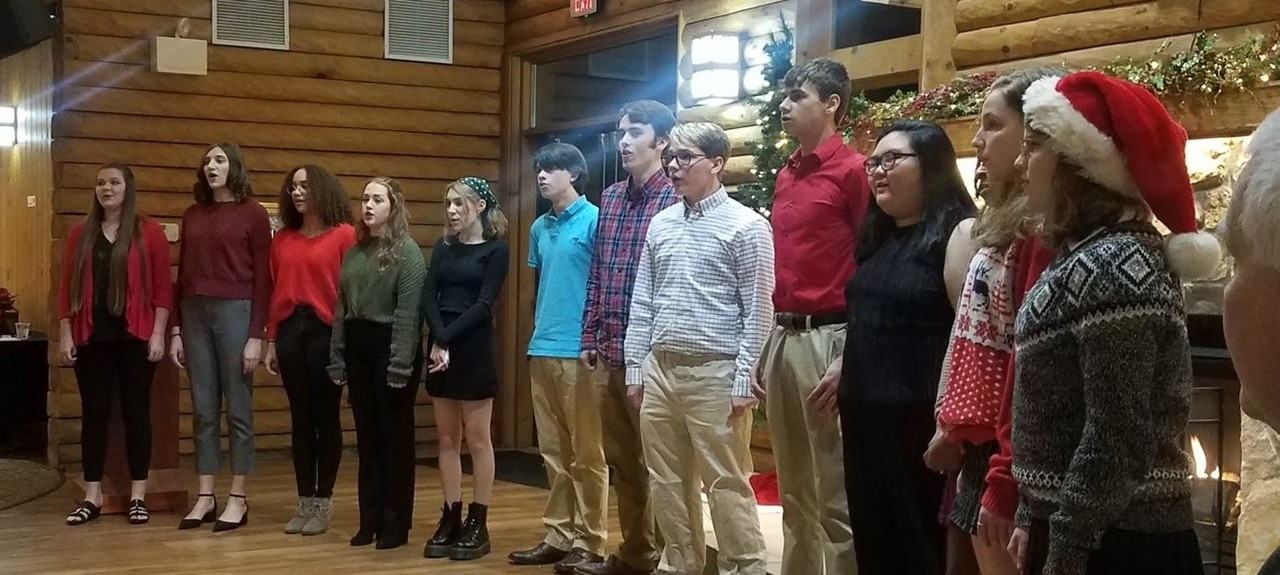 Avonworth Chamber Choir performing at a Christmas Party at the Mayernik Center...12 students standing and singing in a line.