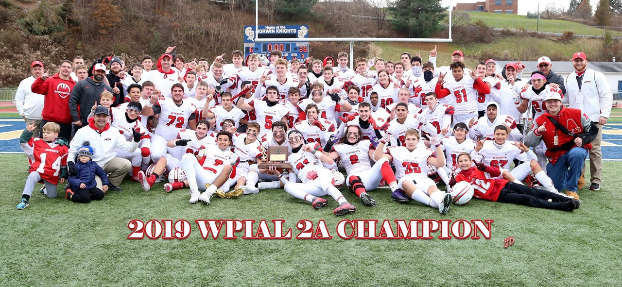 Photo of the Avonworth Football Team on the field with the WPIAL 2A Champion trophy on the field in Norwin after winning the championship