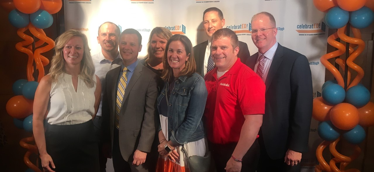 Photo of Avonworth administrators and teachers in front of the CelebratED banner with balloons on each side at an event this fall where the district was recognized for its commitment to transformative change