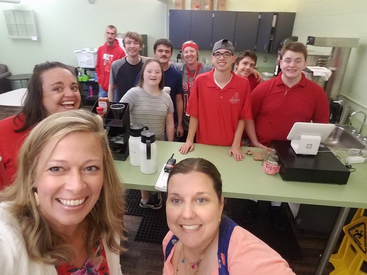 Lopes Lounge -Opening Day...students working in the Lopes Lounge and serving coffee.  All people (6 students, 2 teachers and HS Principal) in the photo are smiling in a selfie.