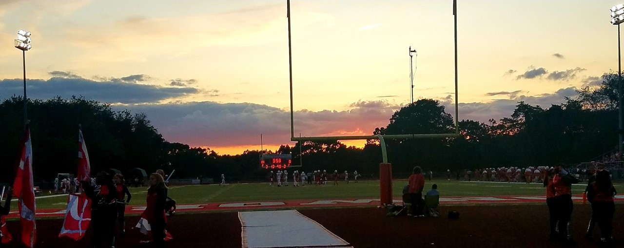 Sunset Photo of AHS Football Game - 8/23/19...photo from the end zone shows players on the fields and the band getting ready to play at halftime.