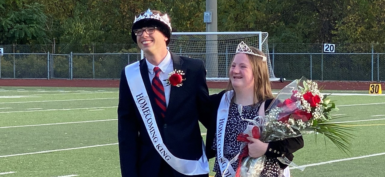 Photo of the ASD Homecoming King and Queen standing on the football field.