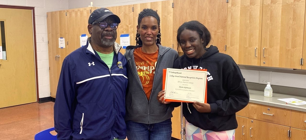 Photo of a student with her parents holding the certificate she was awarded for being named an African American Scholar