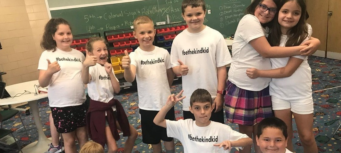 photo of primary and elementary students in a classroom wearing their #bethekindkid t-shirts and giving a thumbs up