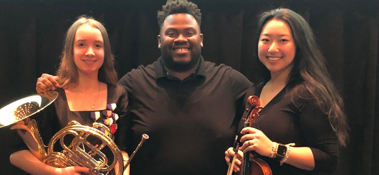 Photo of Lea, Mr. Guess, and Claire in that order.  Lea and Clair are posing with their instruments.