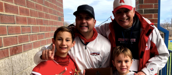 Photo of Mike Mancuso holding the WPIAL Championship with his family around him.