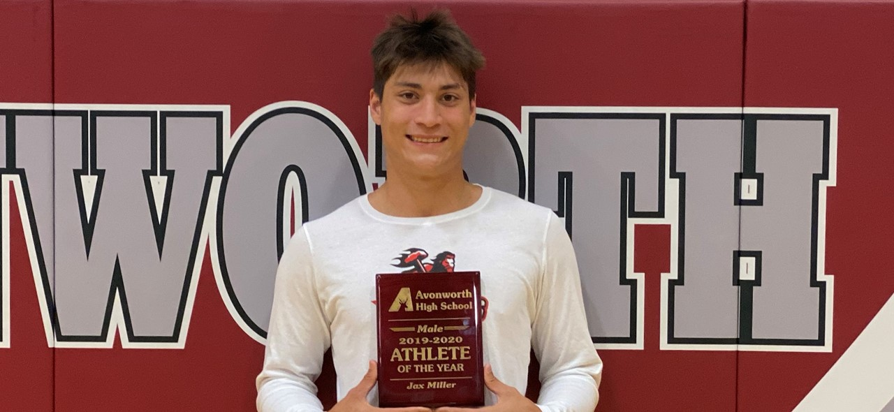 Photo of Jax Miller holding his Male Athlete of the Year plaque in front of the pads in the gym that have the word Avonworth on them.