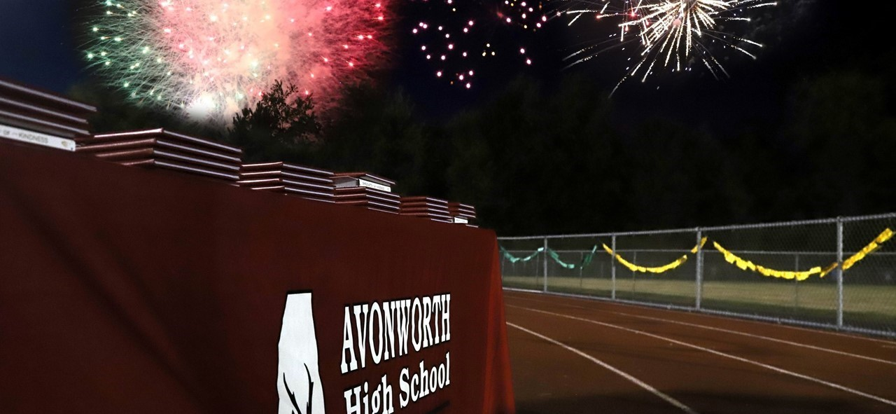 Photo of a table on the high school track with the diplomas on it for graduation with fireworks in the background
