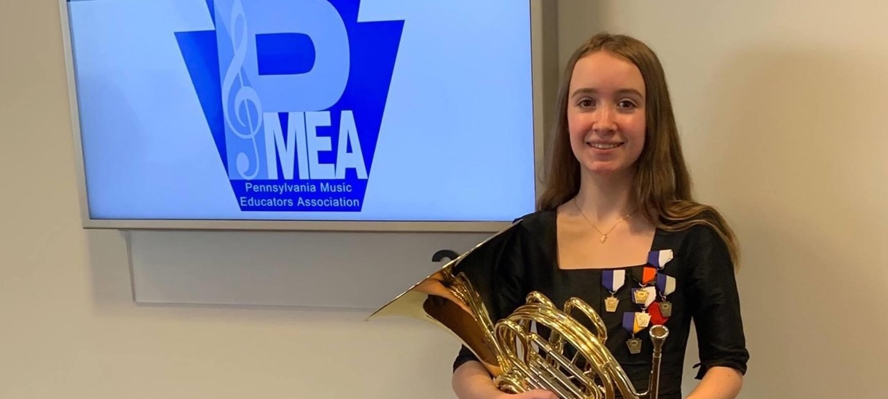 Photo of Lea Helsel holding her French horn in front of a sign that says PMEA.