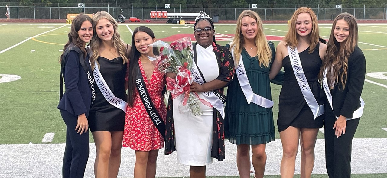 Photo of the 2021 Avonworth High School Homecoming Court on the sideline of the football field.  The photo is of 7 of our female students.
