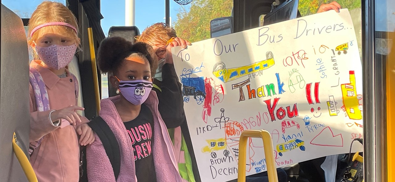 Photo of an Avonworth bus driver holding up a thank you sign with two students standing to her right.  The driver is in her driver's seat and the students are standing next to her.