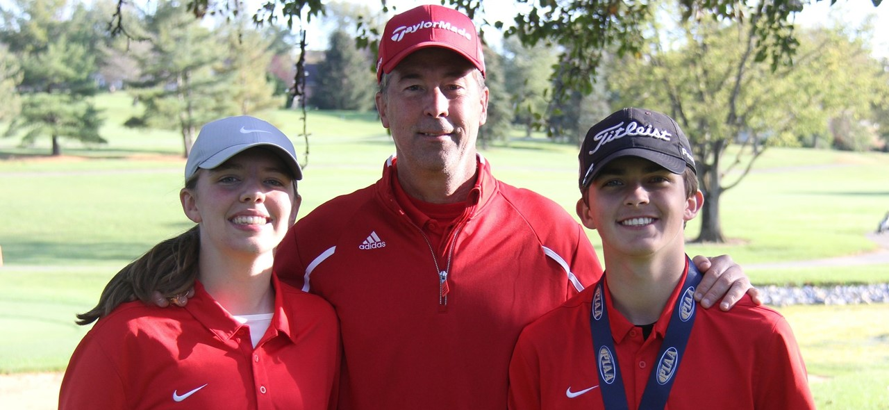 Photo of two Avonworth golfers and their coach outside at a golf course where they competed in the state championship.  One student, Kai, is wearing his medal. He finished in 2nd place.