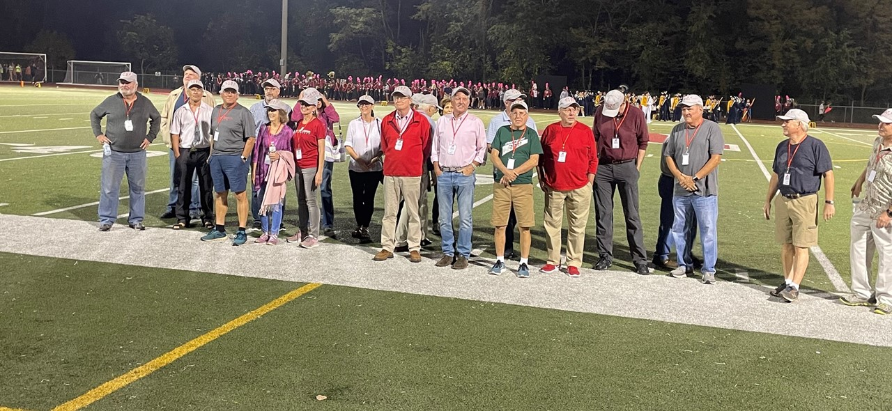 Photo of the class of 1971 standing on the sideline of the football field during halftime as they were recognized at the homecoming game on October 15, 2021.