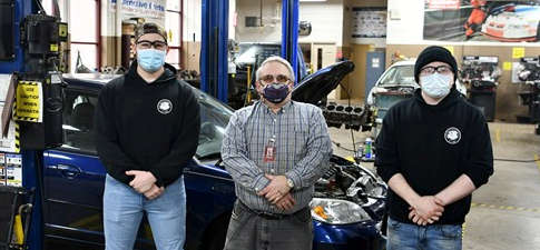 Photo of senior jake abbott standing with another student and their teacher in the automotive garage at Beattie Career Center.  There is a car behind them.