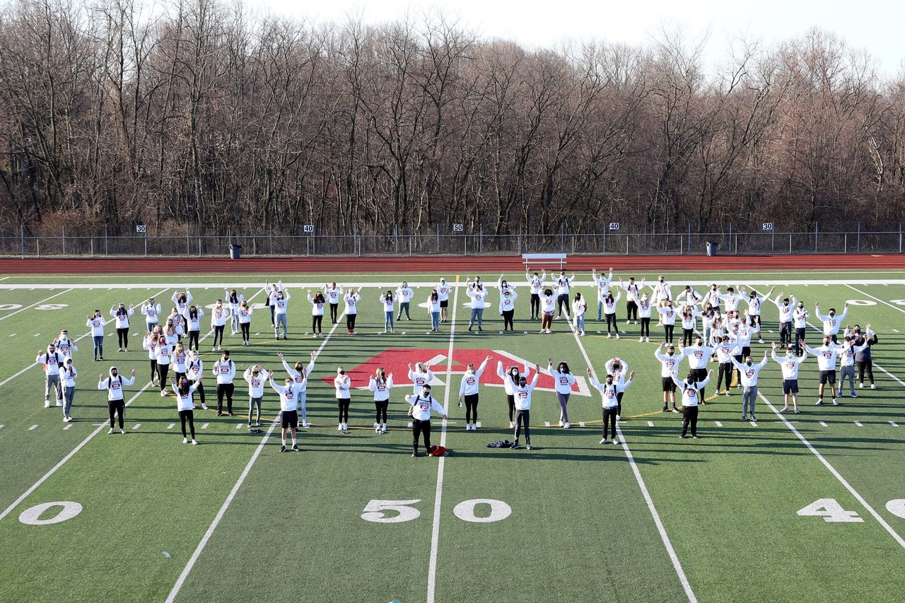 """Picture includes members of the senior class standing around the """"A"""" on the football field together waving up at the camera."""