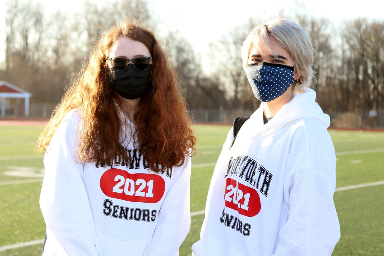 Two 12th grade students standing outside with masks