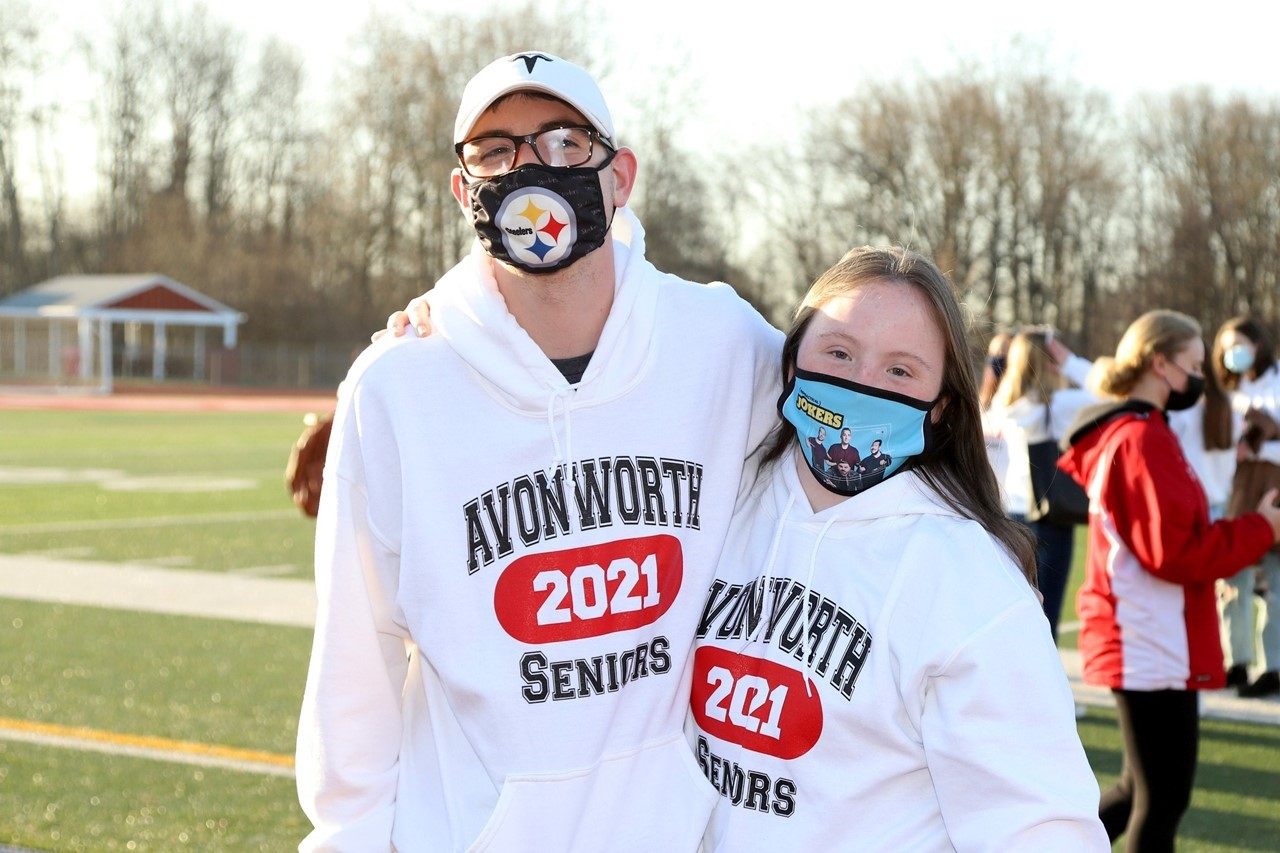 Two 12th grade students standing outside with masks on the football field