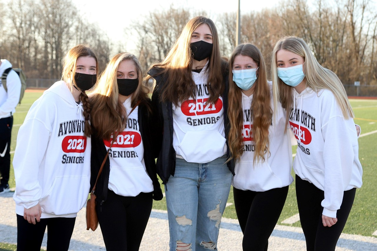 Five 12th grade students standing outside with masks on the football field