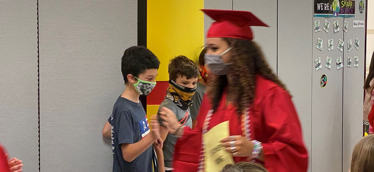 photo of a class of 2021 grad walking through the primary center and giving a student a high five.  three students are in the picture and all have masks on