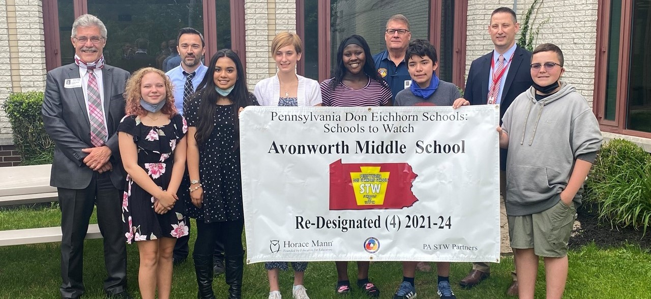 Image of students and middle school principal Mr. Hall holding a banner indicating the 4th re-designation of the middle school for the Schools To Watch Program