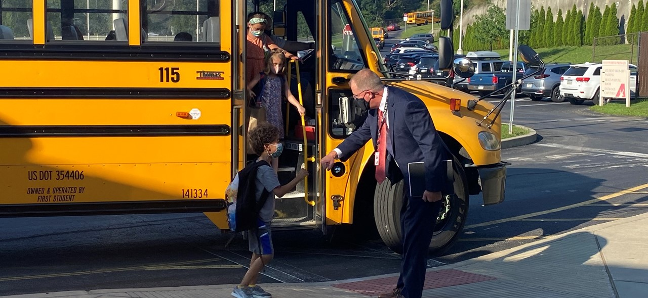 Photo of Dr. Hadley greeting primary students as they get off the school bus on the first day of school.
